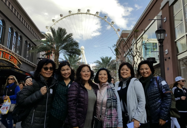 Foodie friends posing for a photo in front of the High Roller at the Linq Promenade on a private food tour in Las Vegas